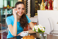 Smiling girl drinking a cappuccino and having a call with her sm Stock Images