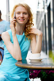 Smiling girl drinking coffee in cafe and talking on smartphone Royalty Free Stock Photos