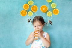 Smiling girl drinks fresh orange juice Royalty Free Stock Images