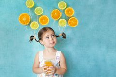 Smiling girl drinks fresh orange juice Stock Photography