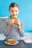 Smiling girl eat healthy sandwich with salad, avocado and other. Vegetables in her room Stock Photography