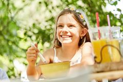 Smiling girl is eating cereal for breakfast. In summer at summer camp Stock Photography
