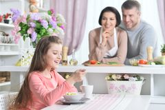 Smiling girl eating at kitchen. With parents on background Stock Photography