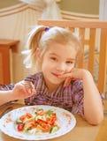 Smiling girl eating salad Royalty Free Stock Photo
