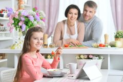 Smiling girl eating and using tablet at kitchen with parents Stock Photography
