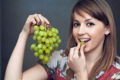 The smiling girl is eatting  grapes Stock Photography