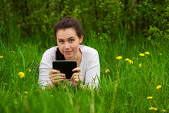 Smiling girl with ebook lying on the grass Royalty Free Stock Photography