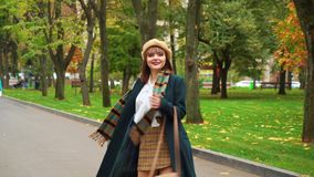 Smiling girl in elegant outfit walking in autumn park
