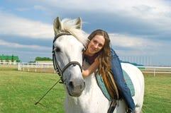 Smiling girl embraces a white horse Royalty Free Stock Photos
