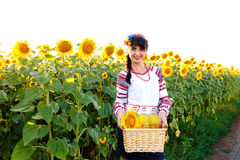 Smiling girl in embroidery holding a basket with sunflower oil Stock Photo