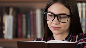 Smiling girl enjoy reed story in bookstore closeup. Schooling academical concept. Young female 20s successful persone read book in class room. Pretty teenager stock video footage