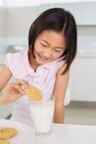 Smiling girl enjoying cookies and milk at home Royalty Free Stock Photos