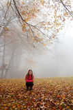 Smiling girl enjoying day in foggy autumn forest. Royalty Free Stock Images