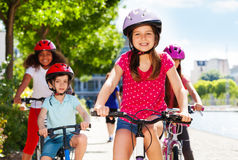 Smiling girl enjoying riding bicycle with friends Stock Images