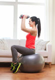 Smiling girl exercising with fitness ball Stock Photos