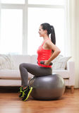 Smiling girl exercising with fitness ball Royalty Free Stock Photos