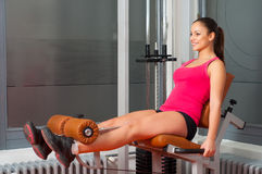 Smiling girl exercising legs in the gym Stock Photo