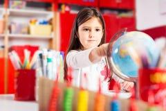 Smiling girl exploring globe Stock Images