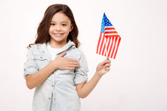 Smiling girl expressing love to her nation in the studio. Proud for my nation. Cheerful smiling happy girl holding the American flag and touching her chest while Stock Image
