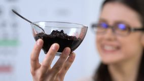 Smiling girl in eyeglasses showing bilberry at camera, delight for eyes health. Stock footage stock video