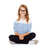 Smiling girl in eyeglasses sitting on floor Royalty Free Stock Photo