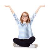 Smiling girl in eyeglasses sitting on floor Royalty Free Stock Photo