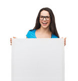 Smiling girl with eyeglasses and white blank board. Vision, health, advertisement and people concept - smiling girl wearing eyeglasses with white blank board royalty free stock images