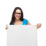 Smiling girl with eyeglasses and white blank board. Vision, health, advertisement and people concept - smiling girl wearing eyeglasses pointing finger to white stock photography