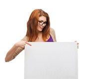 Smiling girl with eyeglasses and white blank board. Vision, health, advertisement and people concept - smiling girl wearing eyeglasses pointing finger to white royalty free stock photo