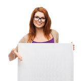 Smiling girl with eyeglasses and white blank board. Vision, health, advertisement and people concept - smiling girl wearing eyeglasses pointing finger to white stock images
