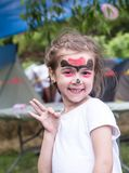 Smiling girl with face art painting like tiger, little boy making face painting, halloween party, child with funny face painting. Little cute boy with faceart stock photography