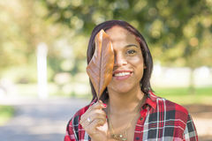 Smiling girl face is covered with old tree leaf, outdoor. Royalty Free Stock Image