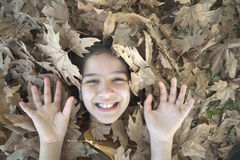 Smiling girl face and hands in the leaves Royalty Free Stock Photo