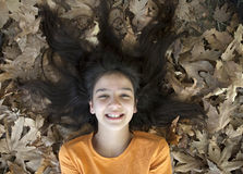 Smiling girl face in the leaves Stock Image