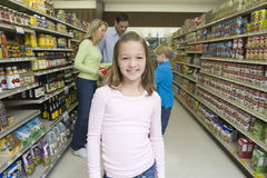 Smiling Girl With Family Shopping In Supermarket Royalty Free Stock Photos