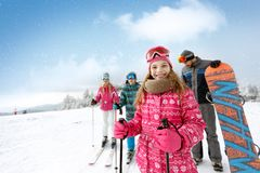 Smiling girl with family on ski terrain. Ready for skiing stock image