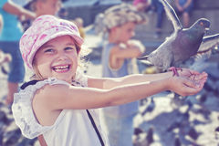 Smiling girl feeding pigeon Stock Photography
