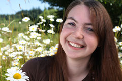 Smiling girl in field of daisies royalty free stock photos