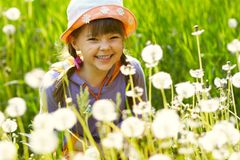 Smiling girl in a field of dandelions Stock Photography