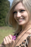 The smiling girl with a field flower Stock Photography