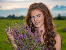 Smiling girl in a field with lavender flowers in her hands. Young woman outdoors with a purple bouquet. Closeup portrait of a happy woman on nature stock photography
