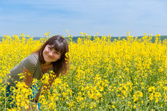 Smiling girl among a field of yellow flowers Royalty Free Stock Photos