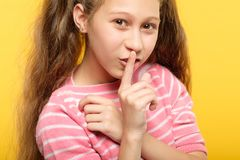 Smiling girl finger lips naughty secret conspiracy. Smiling girl with finger on lips. naughty child secret and conspiracy royalty free stock photography