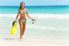 Smiling girl with fins and mask walking on coast Stock Photo
