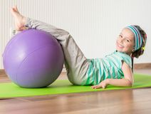 Little girl doing gymnastic exercises. Smiling girl with the fitness ball at home Royalty Free Stock Image
