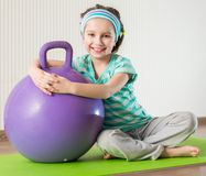 Little girl doing gymnastic exercises. Smiling girl with the fitness ball at home Stock Photos