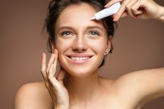 Smiling girl with flawless skin appling treatment cream on beige background stock photo