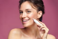 Smiling girl with flawless skin appling treatment cream stock photo