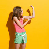 Smiling girl flexing muscles Stock Photos