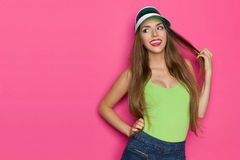 Smiling Girl Flirts. Smiling girl in lime green shirt, green sun visor and jeans shorts holding her long hair and looking away. Waist up studio shot on yellow Stock Photo